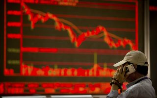 A Chinese investor talks on his cellphone as he monitors stock prices at a brokerage house in Beijing Thursday, Aug. 9, 2018. Asian stock markets were mixed on Thursday with Chinese stocks outperforming the region, as investors watched the latest developments on trade. (AP Photo/Mark Schiefelbein)