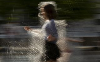 A girl cools herself running through a fountain at a park in Moscow, Russia, Friday, Aug. 3, 2018. The hot weather in Moscow is continuing, with temperatures forecast to reach 30 degrees Celsius (86 Fahrenheit) . (AP Photo/Alexander Zemlianichenko)