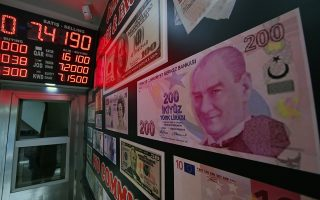 CORRECTING CAPTION BYLINE TO LEFTERIS PITARAKIS - An oversized copy of a 200 Turkish lira banknote, featuring a photo of modern Turkey's founder Mustafa Kemal Ataturk decorates a currency exchange shop in Istanbul. The Turkish lira has nosedived in value in the past week over concerns about Turkey's President Recep Tayyip Erdogan's economic policies and after the United States slapped sanctions on Turkey angered by the continued detention of an American pastor. (AP Photo/Lefteris Pitarakis)