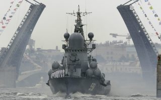 A warship floats past the Dvortsovy (Palace) drawbridge rising above the Neva River during a Naval parade rehearsal in St.Petersburg, Russia, Thursday, July 26, 2018. The celebration of Navy Day in Russia is traditionally marked on the last Sunday of July and will be celebrated on July 29 this year. (AP Photo/Dmitri Lovetsky)