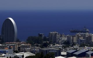 In this Friday, July 6, 2018 photo, shows the Oval building, left, one of a number of new high-rises transforming the skyline view, of the southern coastal city of Limassol in the eastern Mediterranean island of Cyprus. The oval-shaped building with gleaming metal skin, set no more than 100 meters from the sea on a Mediterranean island, resembles a sci-fi portal into another dimension as it reflects the intense mid-July sun. It is one of about a dozen high-rises transforming the skyline of a city in southern Cyprus as the island-nation emerges from a deep financial crisis. (AP Photo/Petros Karadjias)