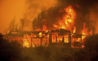 FILE - In this Monday, July 30, 2018, file photo, a home burns as the River Fire rages near Finley, Calif. Authorities say a rapidly expanding Northern California wildfire burning over an area the size of Los Angeles has become the state's largest blaze in recorded history. It's the second year in a row that California has recorded the state's largest wildfire. (AP Photo/Noah Berger, File)