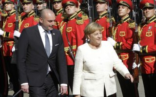 German Chancellor Angela Merkel, right, and Georgian Prime Minister Mamuka Bakhtadze attend a welcome ceremony in Tbilisi, Georgia, Thursday Aug. 23, 2018. Merkel is on an official visit to Georgia. (AP Photo/Shakh Aivazov)