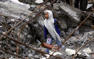A young Acehnese girl walks among the rubble of a mosque destroyed by Tuesday's earthquake in Blang Mancung, Aceh province, Indonesia, Thursday, July 4, 2013. The death toll from the earthquake that hit Indonesia's Aceh province earlier this week has reached 30, and police and soldiers are searching the debris for another 12 people believed missing, officials said Thursday.  (AP Photo/Binsar Bakkara)