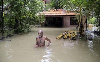 An elderly man wades through flood waters to reach a boat carrying food supplies for stranded people in Chengannur in the southern state of Kerala, India, Sunday, Aug.19, 2018. Some 800,000 people have been displaced and over 350 have died in the worst flooding in a century. (AP Photo/Aijaz Rahi)