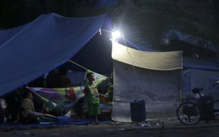 A boy stands in front of a tent at a temporary shelter after being displaced by Sunday's earthquake in North Lombok, Indonesia, Wednesday, Aug. 8, 2018. Aid has begun reaching isolated areas of the Indonesian island struggling after an earthquake killed over 100 people as rescuers intensify efforts to find those buried in the rubble. (AP Photo/Tatan Syuflana)