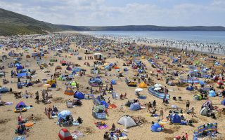 People relax on Woolacombe Beach as another spell of warm weather hits the UK, in North Devon, England, Sunday, Aug. 5, 2018. (Ben Birchall/PA via AP)