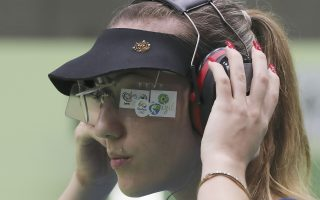Anna Korakaki of Greece adjusts her ear protector during the women's 10-meter air pistol qualification at Olympic Shooting Center at the 2016 Summer Olympics in Rio de Janeiro, Brazil, Sunday, Aug. 7, 2016. Korakaki won the bronze medal for the competition. (AP Photo/Eugene Hoshiko)