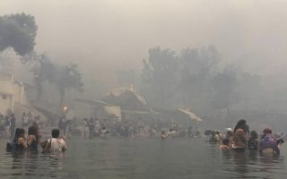 In this Monday, July 23, 2018 image from video provided by Elia Kallia, people escaping wildfires wade into the waters of the