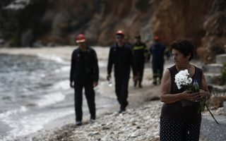 epa06914199 Greek firefighters search for missing people, as Fotini Matrakidis holds flowers next to the point where a six month baby died, following a deadly forest fire in Mati, a northeast suburb of Athens, Greece, 27 July 2018. The confirmed death toll from forest fires that raged through seaside resorts near the Greek capital Athens has increased to 87. According to an announcement by Fire Brigade, the search for more missing persons in the burnt out buildings in eastern Attica is continuing.  EPA/YANNIS KOLESIDIS