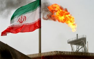 FILE PHOTO: A gas flare on an oil production platform in the Soroush oil fields is seen alongside an Iranian flag in the Persian Gulf, Iran, July 25, 2005. REUTERS/Raheb Homavandi/File Photo