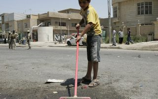 A boy cleans the site of a bomb attack in Palestine Street in northeastern Baghdad June 21, 2011. A roadside bomb killed an Iraqi soldier and wounded five people, including three soldiers, in Palestine Street in northeastern Baghdad, an Interior Ministry source said.  REUTERS/Ali al-Mashhadani (IRAQ - Tags: CIVIL UNREST)