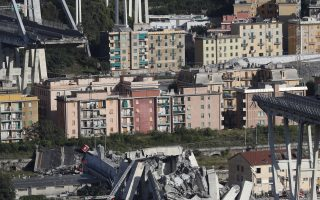 A view of the Morandi highway bridge after a section of it collapsed, in Genoa, northern Italy, Tuesday, Aug. 14, 2018. A large section of the bridge collapsed over an industrial area in the Italian city of Genova during a sudden and violent storm, leaving vehicles crushed in rubble below. (AP Photo/Antonio Calanni)