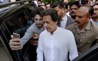 A Pakistani takes selfie with Imran Khan, center, head of the Pakistan Tehreek-e-Insaf party, as he leaves a party meeting in Islamabad, Pakistan, Monday, Aug. 6, 2018. The party won the most parliament seats in last month's general elections and is expected to form a governing coalition later this month. (AP Photo/Anjum Naveed)