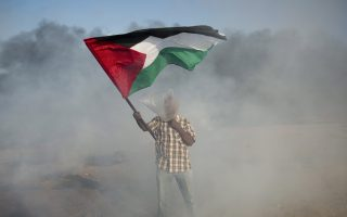 A Palestinian protester wears a plastic bag on his head as a protection from teargas as he waves a national flag during a protest at the Gaza Strip's border with Israel, Friday, Aug.10, 2018. Violence erupted at the Gaza border Friday after the territory's militant Islamic Hamas rulers and Israel appeared to be honoring a cease-fire that ended two days of intense violence amid efforts by neighboring Egypt to negotiate between the two sides. (AP Photo/Khalil Hamra)