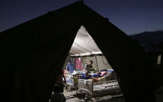 In this Tuesday, Aug. 7, 2018, photo, villagers injured in an earthquake are tended to inside a makeshift hospital in Tanjung, North Lombok, Indonesia. (AP Photo/Tatan Syuflana)