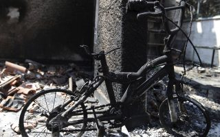 In this Wednesday, July 25, 2018 photo, a burnt bicycle with training wheels stands at the balcony of a destroyed house in Mati, east of Athens. More than 86 people were either killed by the flames or drowned on Monday's wildfire as they tried to flee the fire into the nearby sea, waiting for hours in the water for rescue from local fishermen and private boat owners who saved many. (AP Photo/Thanassis Stavrakis)