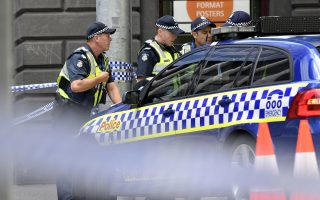 Victorian police man a road block near the site where a car struck pedestrians in the central business district of Melbourne, Australia, Friday, Jan. 20, 2017. A man deliberately drove into a street crowded with pedestrians on Friday, killing people, police said. Officials said the incident had no links to terrorism. (AP Photo/Andrew Brownbill)