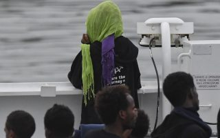 Migrants stand on the deck of the Italian Coast Guard ship Diciotti, moored at the Catania harbor, Tuesday, Aug. 21, 2018. One and seventy-seven migrants rescued at sea remained aboard the Italian Coast Guard ship Diciotti Tuesday morning as the Italian government refused to let them disembark in the port of Catania until other European countries agree to take them.The Diciotti arrived in the port of Catania late Monday night after spending days off the Italian coast as the Italian and Maltese government bickered over where they will be taken. (AP Photo/Salvatore Cavalli)