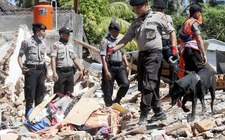 epa06934481 Indonesian K-9 dog police officers search for victims at a collapsed house in Tanjung, West Nusa Tenggara, Indonesia, 08 August 2018. According to media reports, a 7.0 magnitude quake hit the Indonesian island of Lombok on 05 August, killing at least 105 people. Several aftershocks have been detected and hundreds of foreign tourists are being evacuated from the island.  EPA/ADI WEDA