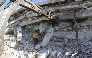 This photo provided by the Syrian Civil Defense White Helmets, which has been authenticated based on its contents and other AP reporting, shows Syrian White Helmet civil defense workers at the scene of an explosion that brought down a five-story building, in the village of Sarmada, near the Turkish border, north Syria, Sunday, Aug. 12, 2018. Syrian opposition activists say the explosion killed several people and wounded many others. The cause of the blast wasn't immediately known. (Syrian Civil Defense White Helmets via AP)