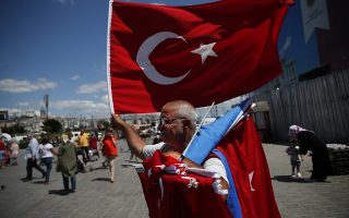 A vendor offers Turkish flags for sale at a market in Istanbul, Monday, Aug. 13, 2018. Turkey's central bank announced a series of measures on Monday to free up cash for banks as the country grapples with a currency crisis sparked by concerns over President Recep Tayyip Erdogan's economic policies and a trade and diplomatic dispute with the United States. (AP Photo/Lefteris Pitarakis)