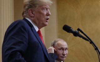 Russian President Vladimir Putin, center, adjusts his earpiece as he listen to U.S. President Donald Trump, left, speak during their joint news conference at the Presidential Palace in Helsinki, Finland, Monday, July 16, 2018. (AP Photo/Pablo Martinez Monsivais)