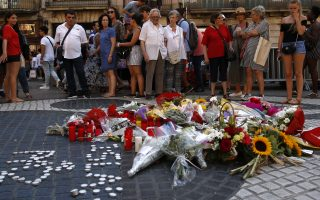 People stand next to a memorial tribute of flowers, messages and candles on Barcelona's historic Las Ramblas in Barcelona, Thursday, Aug. 16, 2018, the day before to the anniversary of the attacks that took place here on Aug. 17, 2017 killing 16 people and injuring more than 120. (AP Photo/Manu Fernandez)