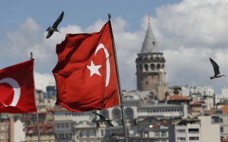 Backdropped by the iconic Galata Tower seagulls fly past Turkish flags in Istanbul, Monday, Aug. 13, 2018. Turkey's central bank announced a series of measures on Monday to free up cash for banks as the country grapples with a currency crisis sparked by concerns over President Recep Tayyip Erdogan's economic policies and a trade and diplomatic dispute with the United States. (AP Photo/Lefteris Pitarakis)