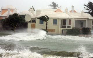 ** FILE ** High waves hit a house in Devonshire Bay, Bermuda, as Hurricane Florence passes near the British island chain, in this Sept. 11, 2006 file photo. Investors who bet against the odds of another devastating Atlantic hurricane season now stand to cash in big-time on