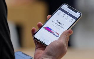 epa06306510 A customer examines the newly released iPhone X at an Apple Store in the Perimeter Mall in Atlanta, Georgia, USA, 03 November 2017. Apple launched its new iPhone X 03 November marking the 10-year anniversary of the first ever iPhone. Apple's new iPhone X goes on sale in more than 55 countries.  EPA/ERIK S. LESSER