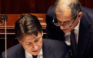Ο πρωθυπουργός Τζουζέπε Κόντε (αριστερά) και ο υπουργός Οικονομικών Τζοβάνι Τρία στο ιταλικό Κοινοβούλιο.