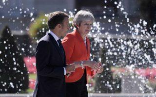 Εμανουέλ Μακρόν και Τερέζα Μέι συνομιλούν μετά την καθιερωμένη, αναμνηστική φωτογραφία των «28» στη χθεσινή, άτυπη Σύνοδο Κορυφής.