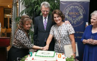 Υπό το βλέμμα του πρέσβη των ΗΠΑ Τζέφρεϊ Πάιατ, η Μαίρη Πάιατ, δεξιά, επίτιμη πρόεδρος της AWOG και η πρόεδρος της οργάνωσης, Μπέσι Σιούτας-Βασιλοπούλου, κόβουν τη γενέθλια τούρτα.