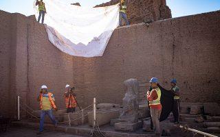 Εργάτες ετοιμάζονται να φωτογραφίσουν εύρημα στον ναό του Κομ Ομπο.