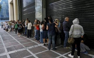 People wait outside a closed branch of Piraeus Bank in Athens, Greece June 27, 2015. The specific branch opens at 10:30 AM local time on Saturdays but it remained closed whille dozens of people lined outside to withdrew cash. Greek Prime Minister Alexis Tsipras called a referendum on austerity demands from foreign creditors on Saturday, rejecting an