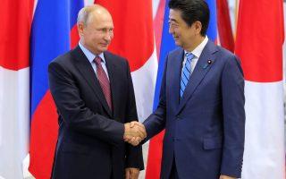 Japanese Prime Minister Shinzo Abe, right, and Russian President Vladimir Putin shake hands prior to their talks at the Eastern Economic Forum in Vladivostok, Russia, Monday, Sept. 10, 2018. (Mikhail Klimentyev, Sputnik, Kremlin Pool Photo via AP)