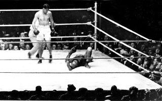 O πρωταθλητής βαρέων βαρών Τζακ Ντέμπσi, ένας από τους δημοφιλέστερους Αμερικανούς αθλητές της πυγμαχίας όλων των εποχών, στέκεται πάνω από τον «σφετεριστή» του τίτλου του, Λούις Φίρπο, τον οποίο έχει μόλις βγάλει νοκ άουτ στον δεύτερο γύρο του αγώνα, στο στάδιο Πόλο Γκράουντς της Νέας Υόρκης, το 1923. (AP Photo)