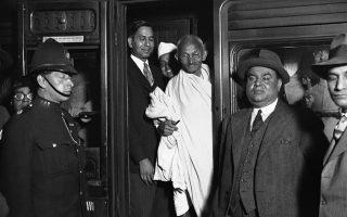 Ο ειρηνιστής ηγέτης του κινήματος για την ινδική ανεξαρτησία, Μαχάτμα Γκάντι, επιβιβάζεται σε ένα τρένο με προορισμό την κομητεία του Λανκασάιρ, στον σιδηροδρομικό σταθμό Γιούστον του Λονδίνου, το 1931. Ο Ινδός ακτιβιστής και πολιτικός δέχτηκε την πρόσκληση μίας εύπορης οικογένειας βιομηχάνων της κωμόπολης του Ντάργουεν, η οποία του εξέφρασε τα προβλήματα που αντιμετωπίζει η βιομηχανία υφασμάτων της περιοχής, λόγω του μποϊκοτάζ που πραγματοποιούσε το ινδικό κίνημα για ανεξαρτησία στα βρετανικά προϊόντα. Μιλώντας σε πλήθος δημοσιογράφων από όλες τις γωνιές το κόσμου, αμετακίνητος και αποφασισμένος, ο Γκάντι τόνισε ότι δεν πρόκειται να υπάρξει κανένας μετριασμός στον αγώνα τον Ινδών για ανεξαρτησία και κανενός είδους στήριξη στη βρετανική βιομηχανία. (AP Photo/Staff/Puttnam)