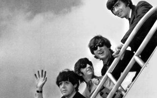 Τα τέσσερα «σκαθάρια» αποχαιρετούν τις Ηνωμένες Πολιτείες και τους χιλιάδες Αμερικανούς θαυμαστές τους, καθώς επιβιβάζονται στο αεροπλάνο που θα μεταφέρει το συγκρότημα πίσω στην Αγγλία, μετά το πέρας της δεύτερης αμερικανικής περιοδείας τους, στο αεροδρόμιο της Νέας Υόρκης, το 1964. (AP Photo)