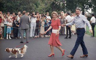 O Αμερικανός πρόεδρος Ρόναλντ Ρήγκαν λέει κάποιο σχόλιο στους δημοσιογράφους, καθώς συνοδεύει τη σύζυγο του, πρώτη κυρία Νάνσυ Ρήγκαν, και τον σκύλο τους, Ρεξ, στον δρόμο τους προς τον Λευκό Οίκο, κατά την επιστροφή τους στην Ουάσιγκτον μετά από ένα Σαββατοκύριακο στο Καμπ Ντέιβιντ, στο Μέριλαντ, την επίσημη θερινή κατοικία του εκάστοτε προέδρου των ΗΠΑ, το 1987. (AP Photo/Charles Tasnadi)