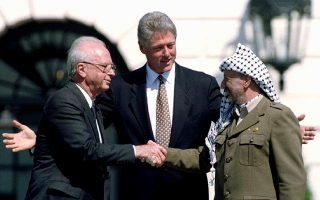 U.S. President Clinton stands with Israeli Prime Minister Yitzhak Rabin (L) and PLO Chairman Yasser Arafat (R) after the signing of the Israeli-PLO peace accord at the White House in Washington in this September 13, 1993 file picture. Palestinians will mark the first anniversary of Arafat's death on November 11, 2005.  REUTERS/Gary Hershorn/Files