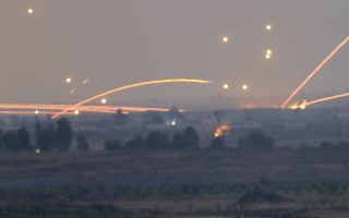 Fire trails and explosions from the fighting between forces loyal to Syrian President Bashar Assad and rebels in southern Syria as seen from the Israeli-controlled Golan Heights, Wednesday, July 25, 2018. (AP Photo/Ariel Schalit)