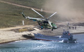 A Russian navy landing vessel unloads an armored vehicle as a military helicopter flies overhead during Russian military maneuvers Vostok 2018 on the training ground
