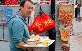REFILE - CORRECTING GRAMMAR A vendor with food passes next to souvenirs with Macedonian flag on at the Old Bazar in Skopje, Macedonia September 29, 2018.REUTERS/Ognen Teofilovski