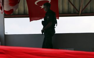 A military police stand guards during a military parade during the highlight of celebrations marking the 44th anniversary of the 1974 Turkish invasion in the Turkish occupied area of the divided capital Nicosia, Cyprus, Friday, July 20, 2018. Cyprus was split into Greek Cypriot south and Turkish Cypriot north in 1974 when Turkey invaded in response to a coup by supporters of union with Greece. (AP Photo/Petros Karadjias)