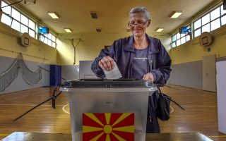 epa07059064 A woman votes in a referendum on the country's name change at a polling station in Skopje, The Former Yugoslav Republic of Macedonia (FYROM), 30 September 2018. Almost two million citizens will vote in a national referendum on 30 September, on whether to change the country's name to 'North Macedonia' to endorse a name deal between FYR of Macedonia and Greece and to qualify for NATO membership.  EPA/GEORGI LICOVSKI