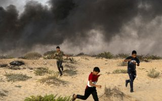 Young Palestinian protesters run from tear gas fired by Israeli soldiers during a protest on the beach near the border with Israel in Beit Lahiya, northern Gaza Strip, Monday, Sept. 10, 2018. Thousands of Palestinians gathered on the beach Monday in a Hamas-led protest to demand end of an 11-year Israeli-Egyptian blockade. (AP Photo/Felipe Dana)