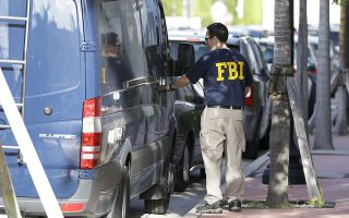 An FBI agent retrieves equipment from a van as he prepares to re-enter the offices of the Confederation of North, Central America and Caribbean Association Football (CONCACAF,) Wednesday, May 27, 2015, in Miami Beach, Fla. Swiss prosecutors opened criminal proceedings into FIFA's awarding of the 2018 and 2022 World Cups, only hours after seven soccer officials were arrested Wednesday pending extradition to the U.S. in a separate probe of