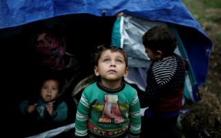 FILE PHOTO: A Syrian refugee boy stands in front of his family tent at a makeshift camp for refugees and migrants next to the Moria camp on the island of Lesbos, Greece, November 30, 2017. REUTERS/Alkis Konstantinidis/File photo